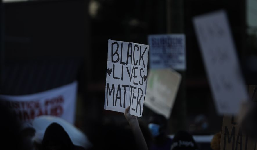 """A """"Black Lives Matter"""" sign is seen during protests on Saturday, June 13, 2020, near the Atlanta Wendy's where Rayshard Brooks was shot and killed by police Friday evening following a struggle in the restaurant's drive-thru line in Atlanta. (AP Photo/Brynn Anderson)"""