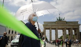 """A protestor wearing an umbrella with the slogan """"Grannies against the right"""" attends the 'This is solidarity' demonstration of the movement Unteilbar (Indivisible), in Berlin, Sunday, June 14, 2020. The demonstration against racism, anti-semitism and discrimination is supported by several anti-racism and anti-fascism organizations and takes place in the wake of the recent killing of George Floyd by police officers in Minneapolis, USA, that has led to protests in many countries and across the US. (AP Photo/Markus Schreiber)"""