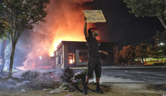 A person holds a sign as a Wendy's restaurant burns Saturday, June 13, 2020, in Atlanta after demonstrators set it on fire. Demonstrators were protesting the death of Rayshard Brooks, a black man who was shot and killed by Atlanta police Friday evening following a struggle in the Wendy's drive-thru line. (Ben GrayAtlanta Journal-Constitution via AP)