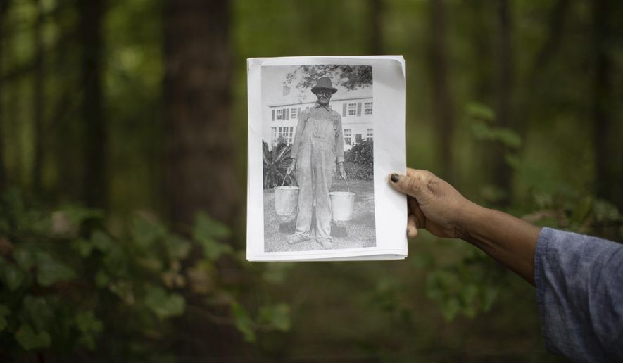 In this Friday, June 5, 2020 photo, Gloria Anderson Jefferson holds a photo of an unidentified man born on the Welaunee plantation she believes is related to her and who is likely buried in New Hope Cemetery located which may be located under a section of the Miccosukee Greenway near Tallahassee, Fla. (Tori Lynn Schneider/Tallahassee Democrat via AP)