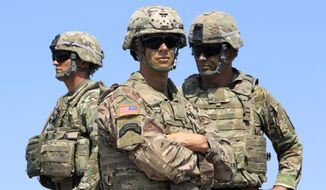 In this  Wednesday, Aug. 9, 2017, photo US soldiers take part in NATO-led Noble Partner 2017 multinational military exercises at the military base of Vaziani, outside Tbilisi, Georgia. After more than a year of thinly veiled threats that the United States could start pulling troops out of Germany unless the country increases its defense spending to NATO standards, President Donald Trump appears to be going ahead with the hardball approach with a plan to reduce the American military presence in the country by more than 25 percent. (AP Photo/Shakh Aivazov) **FILE**