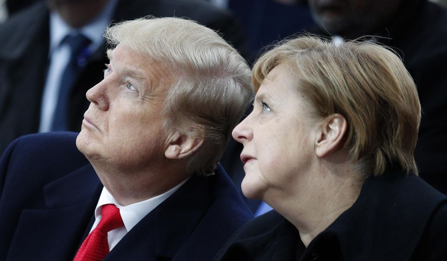 In this Sunday, Nov. 11, 2018, file photo, U.S President Donald Trump and German Chancellor Angela Merkel attend ceremonies at the Arc de Triumphe in Paris. After more than a year of thinly veiled threats that the United States could start pulling troops out of Germany unless the country increases its defense spending to NATO standards, President Donald Trump appears to be going ahead with the hardball approach with a plan to reduce the American military presence in the country by more than 25 percent. (AP Photo/Francois Mori, Pool, File)