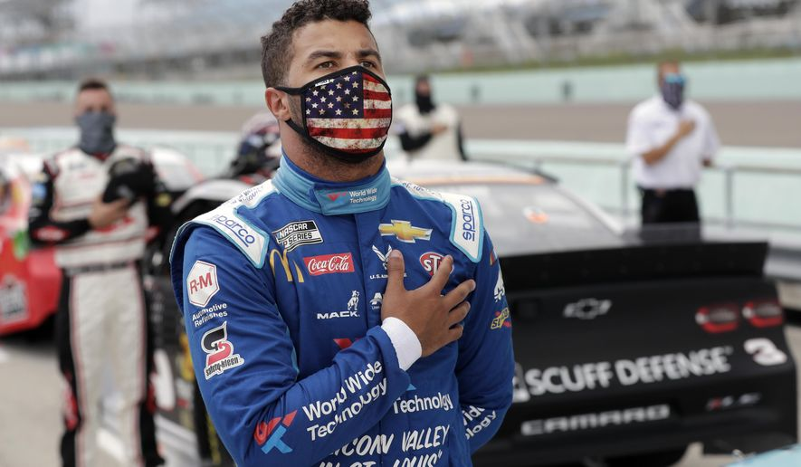 Bubba Wallace stands for the national anthem before a NASCAR Cup Series auto race Sunday, June 14, 2020, in Homestead, Fla. (AP Photo/Wilfredo Lee) ** FILE **