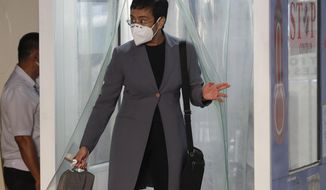 Rappler CEO and Executive Editor Maria Ressa, wearing a protective mask, exits a disinfection area before attending a court hearing at Manila Regional Trial Court, Philippines on Monday June 15, 2020. Ressa's verdict is expected to be announced Monday for a cyber libel case. (AP Photo/Aaron Favila)