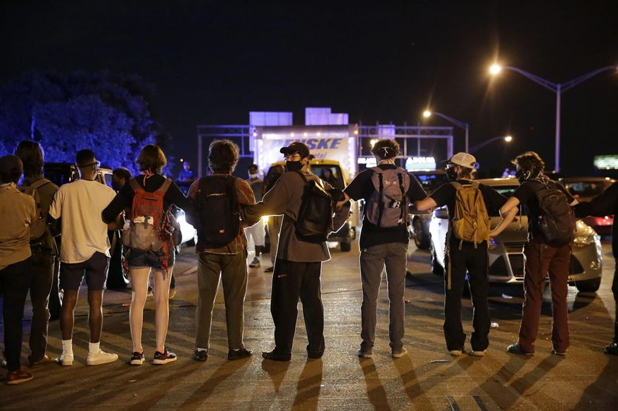 A person looks back as officials move closer during protests Saturday, June 13, 2020, near the Atlanta Wendy's where Rayshard Brooks was shot and killed by police Friday evening following a struggle in the restaurant's drive-thru line in Atlanta. (AP Photo/Brynn Anderson)
