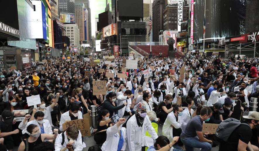 Protesters kneel in Times Square in New York, Tuesday, June 2, 2020. The New York City immortalized in song and scene has been swapped out for the last few months with the virus version. In all the unknowing of what the future holds, there's faith in that other quintessential facet of New York City: that the city will adapt. (AP Photo/Seth Wenig)