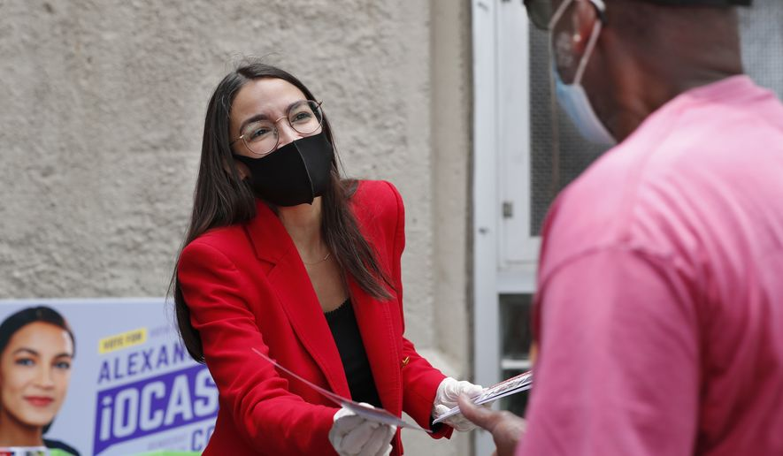 First-term U.S. Rep. Alexandria Ocasio-Cortez, D-New York, left, hands out leaflets explaining how to vote early or by absentee ballot to a pedestrian at the Parkchester subway station in the Bronx borough of New York, Monday, June 15, 2020, in New York. Ocasio-Cortez is running against challenger and former journalist Michelle Caruso-Cabrera and others in New York's June 23 primary. (AP Photo/Kathy Willens)