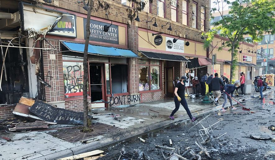 People clean up burned businesses on Saturday, May 30, 2020, after a night of fires and looting following the death of George Floyd. (Associated Press) ** FILE **