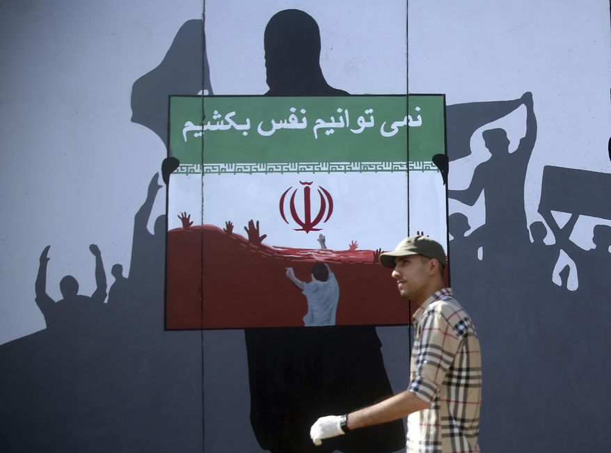 """A man walks past a painting on a wall with writing in the Dari Language reading """"We cannot breath"""" during a protest themed Killings of Afghans in Iran in Kabul, Afghanistan, Monday, June 15, 2020. The violent deaths of Afghan refugees inside Iran has sparked an uproar despite denials from Tehran. (AP Photo/ Rahmat Gul)"""