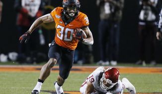 In this Nov. 30, 2019, file photo, Oklahoma State running back Chuba Hubbard (30) carries past Oklahoma linebacker Caleb Kelly during an NCAA college football game in Stillwater, Okla. Hubbard said on Twitter that he won't do anything with the program until there is change after coach Mike Gundy was photographed wearing a T-shirt representing far-right online publication One America News Network. Gundy is seen in a photograph on Twitter wearing the T-shirt with the letters OAN. (AP Photo/Sue Ogrocki) ** FILE **