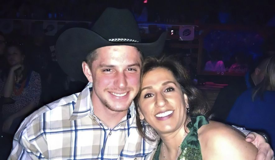 This image provided by Joey Reed, shows Trevor Reed and his mom Paula Reed in 2014 in Arlington, Texas. The parents of Reed, a former U.S. Marine who has been jailed for nearly a year in Moscow on charges that he assaulted police officers, are urging the court system and government to ensure a fair trial for their son. The parents of Trevor Reed spoke Monday to The Associated Press as a Russian court sentenced another American man to more than a decade in prison in an unrelated espionage case. (Joey Reed via AP)