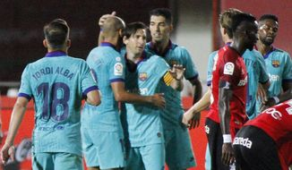 Barcelona's Lionel Messi, center, celebrates with his teammates after scoring his side's fourth goal during the Spanish La Liga soccer match between Mallorca and FC Barcelona at Son Moix Stadium in Palma de Mallorca, Spain, Saturday, June 13, 2020. With virtual crowds, daily matches and lots of testing for the coronavirus, soccer is coming back to Spain. The Spanish league resumes this week more than three months after it was suspended because of the COVID-19 pandemic. (AP Photo/Francisco Ubilla)