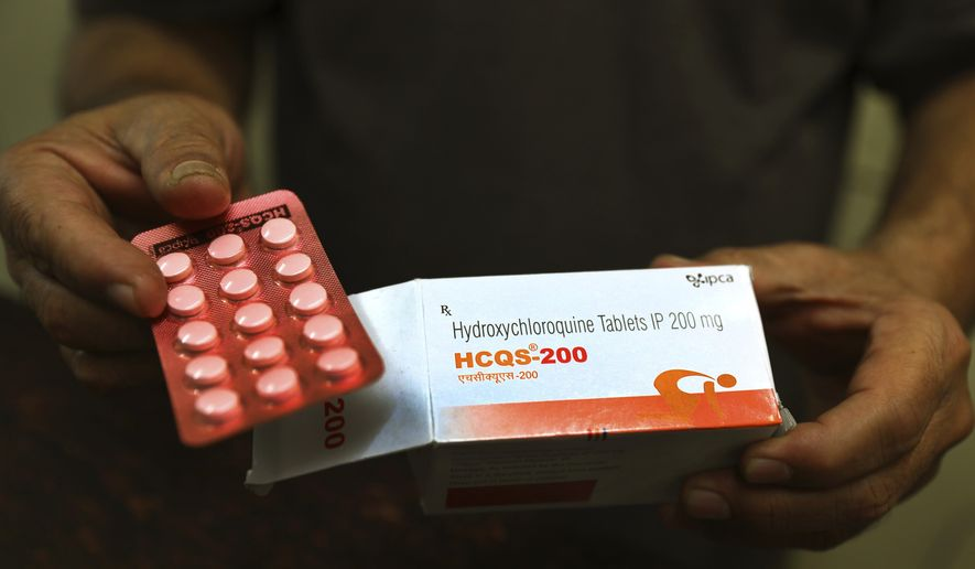In this April 9, 2020, photo, a chemist displays hydroxychloroquine tablets in New Delhi, India. A new peer-reviewed study suggests the drug may help in treating hospitalized COVID-19 patients. (AP Photo/Manish Swarup) **FILE**