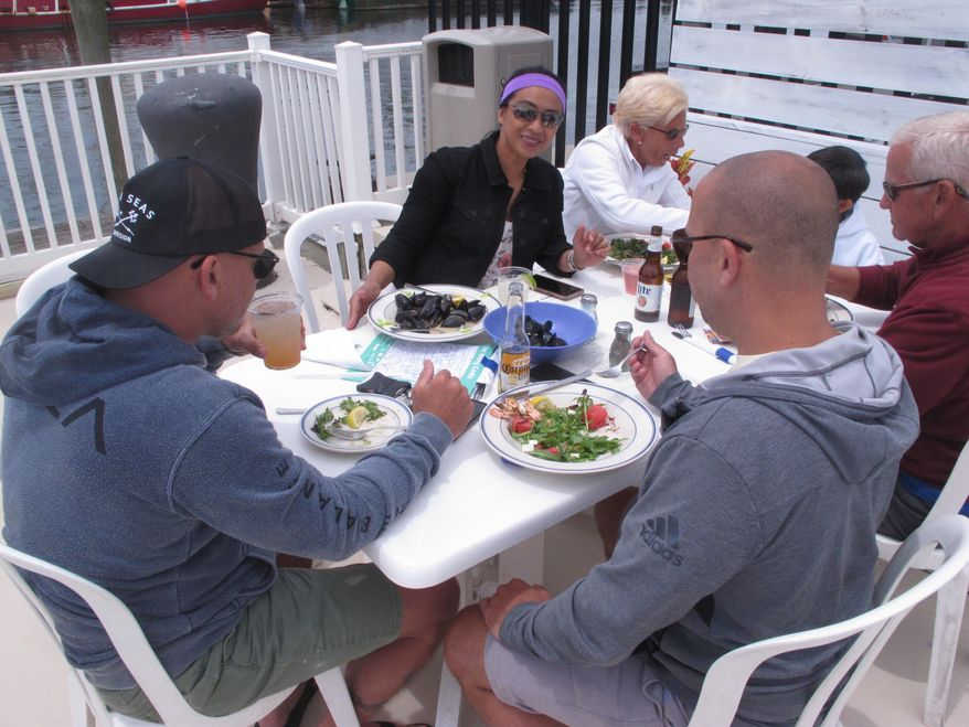 Loralie Lombardo, center, eats lunch with her family at an outdoor seafood restaurant in Point Pleasant Beach, N.J. on June 15, 2020, the first day New Jersey allowed outdoor dining to resume during the coronavirus outbreak. (AP Photo/Wayne Parry)  **FILE**