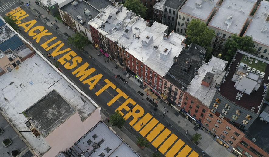 """A giant """"BLACK LIVES MATTER"""" sign is painted in orange on Fulton Street, Monday, June 15, 2020, in the Brooklyn borough of New York. (AP Photo/John Minchillo)"""