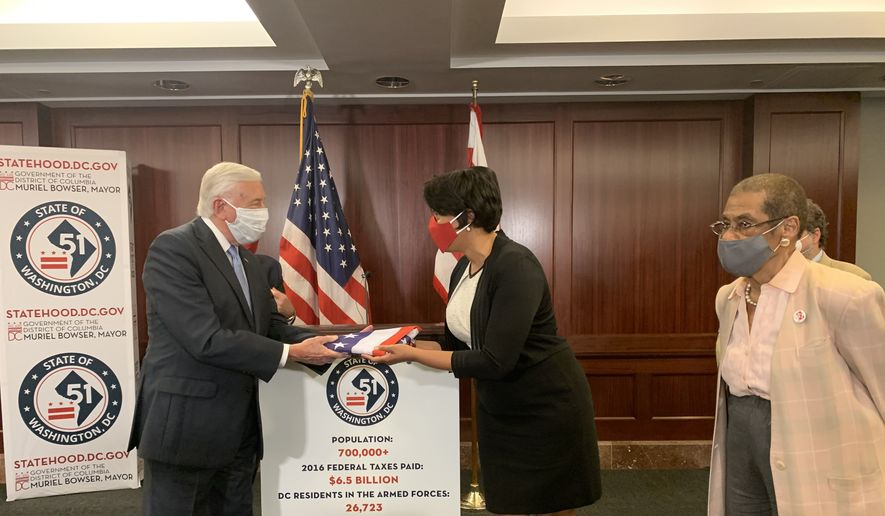 D.C. Mayor Muriel Bowser presents House Majority Leader Steny H. Hoyer with a U.S. flag bearing 51 stars, representing the District of Columbia as a state, during a press conference at the U.S. Capitol on Tuesday, June 16, 2020. The House will vote on D.C. statehood on June 26. (Sophie Kaplan/The Washington Times)