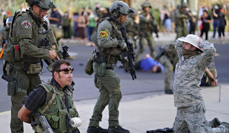 """Albuquerque police detain members of the New Mexico Civil Guard, an armed civilian group, following the shooting of a man during a protest over a statue of Spanish conquerer Juan de Oñate on Monday, June 15, 2020, in Albuquerque, N.M. A confrontation erupted between protesters and a group of armed men who were trying to protect the statue before protesters wrapped a chain around it and began tugging on it while chanting: """"Tear it down."""" One protester repeatedly swung a pickax at the base of the statue. Moments later a few gunshots could be heard down the street and people started yelling that someone had been shot. (Adolphe Pierre-Louis/The Albuquerque Journal via AP)"""