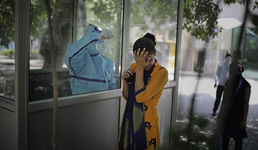 A woman reacts after getting a nasal swab taken to test for the coronavirus in Noida, on the outskirts of New Delhi, India, Tuesday, June 16, 2020. India is the fourth hardest-hit country by the COVID-19 pandemic in the world after the U.S., Russia and Brazil. (AP Photo/Altaf Qadri)