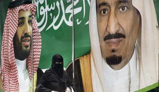 A woman walks past a banner showing Saudi King Salman, right, and his Crown Prince Mohammed bin Salman, outside a mall in Jiddah, Saudi Arabia, Monday, June 15, 2020. (AP Photo/Amr Nabil) ** FILE **