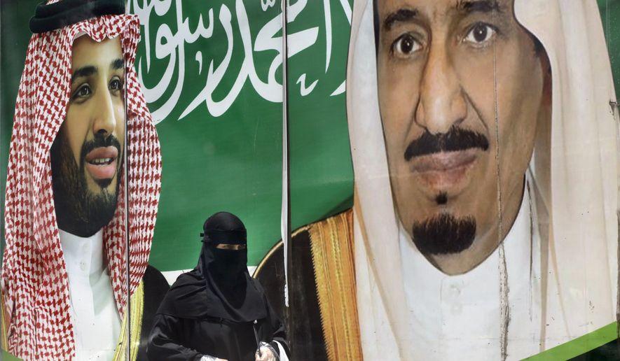 A woman walks past a banner showing Saudi King Salman, right, and his Crown Prince Mohammed bin Salman, outside a mall in Jiddah, Saudi Arabia, Monday, June 15, 2020. (AP Photo/Amr Nabil) ** FILE **