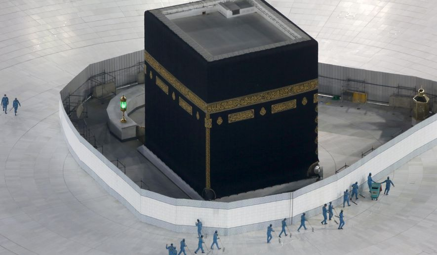 In this March 7, 2020, file photo, workers disinfect the ground around the Kaaba, the cubic building at the Grand Mosque, in the Muslim holy city of Mecca, Saudi Arabia, after authorities emptied Islam's holiest site for sterilization over fears of the new coronavirus. (AP Photo/Amr Nabil, File)