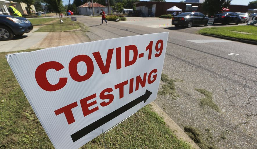 In this Thursday, June 11, 2020 photo, signs line the street along South Church Street in Tupelo, Miss., to let drivers know where to go for free COVID-19 testing at the Family Resource Center. (Thomas Wells/The Northeast Mississippi Daily Journal via AP)