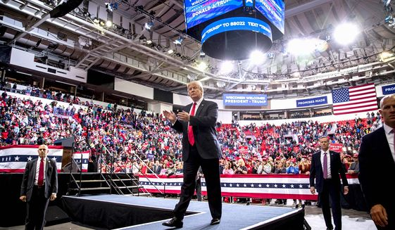 President Trump arrives at a campaign rally in Wisconsin in late 2019, and claps along with a large friendly crowd. (Associated Press)