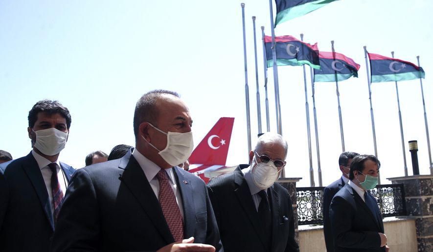 Turkey's Foreign Minister Mevlut Cavusoglu, left, and Muhammed Tahir Siyala, Foreign Minister of Libya's internationally-recognized government, gspeak at the airport, in Tripoli, Libya, Wednesday, June 17, 2020.(Fatih Aktas/Turkish Foreign Ministry via AP, Pool)