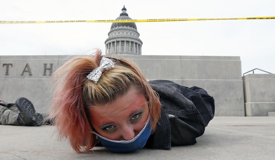 A protester lies down for 8 minutes and 46 seconds during a protest at the Utah State Capitol in Salt Lake City, June 6, 2020. Utah lawmakers have taken a first step toward banning police officers from placing their knees on the necks of people being detained in the type of chokehold used by a Minnesota police officer in the death of George Floyd. (AP Photo/Rick Bowmer) ** FILE **