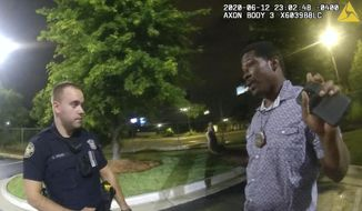 FILE - This screen grab taken from body camera video provided by the Atlanta Police Department shows Rayshard Brooks speaking with Officer Garrett Rolfe, left, in the parking lot of a Wendy's restaurant, late Friday, June 12, 2020, in Atlanta. Rolfe, who fatally shot Rayshard Brooks in the back after the fleeing man pointed a stun gun in his direction, was charged with felony murder and 10 other charges, announced Wednesday, June 17, 2020. Rolfe was fired after the shooting. (Atlanta Police Department via AP)