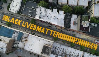 "In this  June 15, 2020, file photo, a giant ""Black Lives Matter"" sign is painted in orange on Fulton Street, Monday, June 15, 2020, in the Brooklyn borough of New York. Black Lives Matter Global Network Foundation, the group behind the emergence of the Black Lives Matter movement, has established a more than $12 million fund to aid organizations fighting institutional racism in the wake of the George Floyd protests. (AP Photo/John Minchillo, File)"