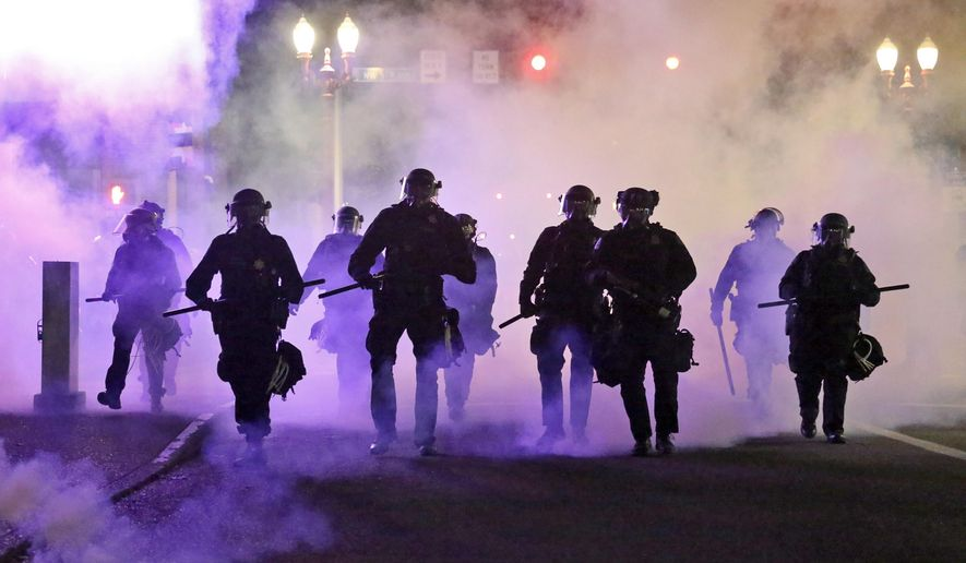 In this March 29, 2020, file photo, police officers walk enveloped by tear gas in Portland, Ore. City commissioners in Portland voted Wednesday, June 17, 2020 to cut nearly $16 million from the Portland Police Bureau's budget in response to concerns about police brutality and racial injustice. The cuts are part of a city budget approved by the commissioners by a 3-1 vote in a contentious meeting.(Dave Killen/The Oregonian via AP, File)