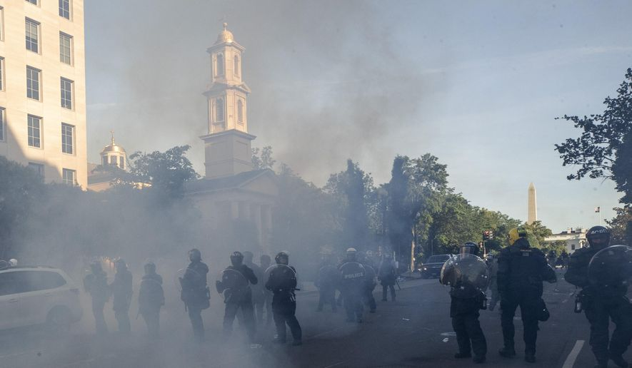 In this June 1, 2020, photo police move demonstrators away from St. John's Church across Lafayette Park from the White House, as they gather to protest the death of George Floyd in Washington. (AP Photo/Alex Brandon) **FILE**