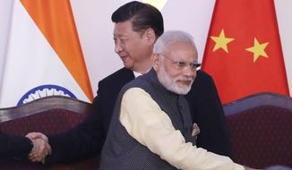 In this Oct. 16, 2016, file photo, Indian Prime Minister Narendra Modi, front and Chinese President Xi Jinping shake hands with leaders at the BRICS summit in Goa, India. India and China sought Wednesday, June 17, 2020, to de-escalate tensions following a fatal clash along a disputed border high in the Himalayas that left 20 Indian soldiers dead. The skirmish Monday in the desolate alpine area of Ladakh, in Kashmir, followed changes by India to the political status of Kashmir amid a geopolitical tug-of-war with the United States in the region. (AP Photo/Manish Swarup, File)