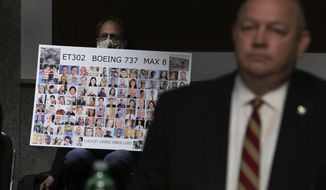 Michael Stumo holds a sign displaying photographs of the individuals who were killed in the March 10, 2019, crash of Ethiopian Airlines flight 302, as Federal Aviation Administration administrator Stephen Dickson testifies during a hearing of the Senate Commerce, Science, and Transportation Committee on Capitol Hill on Wednesday, June 17, 2020, in Washington. (Graeme Jennings/Pool via AP)
