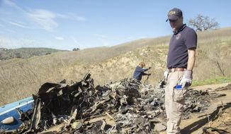 In this Jan. 27, 2020, file photo, provided by the National Transportation Safety Board, NTSB investigators Adam Huray, right, and Carol Hogan examine wreckage as part of the NTSB's investigation of a helicopter crash near Calabasas, Calif. Federal investigators said Wednesday, June 17, 2020, that the pilot of the helicopter that crashed in thick fog, killing Kobe Bryant and seven other passengers, reported he was climbing when he actually was descending. (James Anderson/National Transportation Safety Board via AP, File)  **FILE**