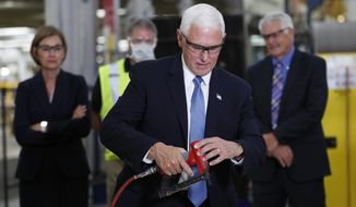 Vice President Mike Pence nails flooring on an RV as he tours Winnebago Industries, Tuesday, June 16, 2020, in Forest City, Iowa. (AP Photo/Charlie Neibergall)