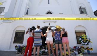 FILE - In this June 18, 2015, file photo, a group of women pray at a makeshift memorial on the sidewalk in front of the Emanuel AME Church in Charleston, S.C. One big change happened in conservative South Carolina after a racist gunman killed nine black people during a Bible study five years ago, the Confederate flag came down. But since then, hundreds of other monuments and buildings named for Civil War figures, virulent racists and even a gynecologist who did painful, disfiguring medical experiments on African American women remain. (AP Photo/Stephen B. Morton, File)