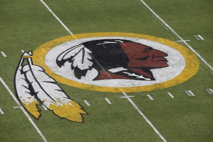 In this Aug. 7, 2014 file photo, the Washington Redskins NFL football team logo is seen on the field before an NFL football preseason game against the New England Patriots in Landover, Md. A group of investment firms are pushing companies like FedEx, which has naming rights for the Redskins stadium, to dissociate from the NFL team unless it changes its name. (AP Photo/Alex Brandon, File)