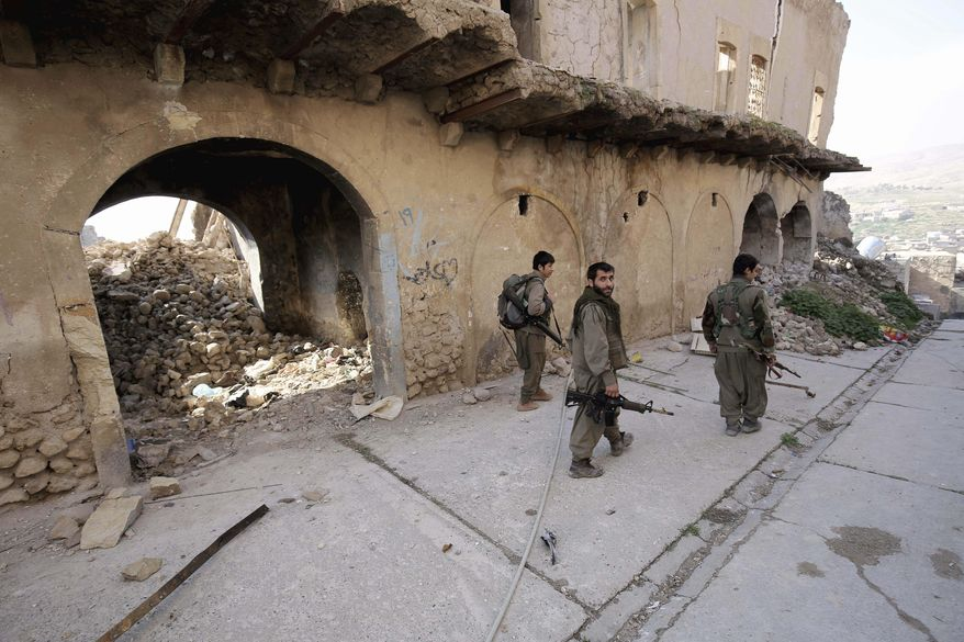 In this Thursday, Jan. 29, 2015, file photo, fighters of the Turkey-based Kurdish Workers' Party (PKK) walk in the damaged streets of Sinjar, Iraq. Turkey said Wednesday, June 17, 2020, it has airlifted troops for a cross-border ground operation against Kurdish militants in northern Iraq. Turkey regularly carries out air and ground attacks against the outlawed Kurdistan Workers Party, or PKK, which maintains bases in northern Iraq. Wednesday's was the first known airborne land offensive.(AP Photo/Bram Janssen, File)