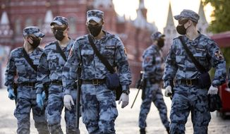 Russian Rosguardia (National Guard) soldiers wearing face masks and gloves to protect against coronavirus, guard an area on Red Square before a rehearsal of the military parade near Red Square in Moscow, Russia, Sunday, June 14, 2020. Last month, Putin ordered an end to the nationwide economic shutdown and set dates for the two main events on his agenda that were postponed due to the coronavirus. (AP Photo/Alexander Zemlianichenko)