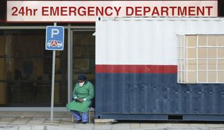 A health worker in personal protective gear takes a break at the Netcare Christiaan Barnard Memorial Hospital in Cape Town, South Africa, Wednesday June 17, 2020. The country now has more than a quarter of the coronavirus cases on the 54-nation African continent with more than 73,000 cases after new, record-high infections were registered in South Africa over the weekend. (AP Photo/Nardus Engelbrecht)
