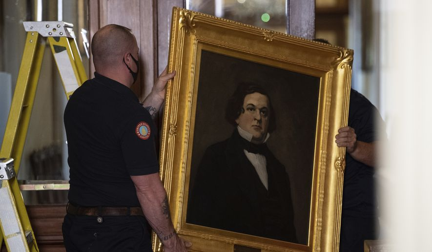 Architect of the Capitol workers remove a portrait of Howell Cobb of Georgia that was hanging in the Speakers Lobby on Capitol Hill, Thursday, June 18, 2020, in Washington. (Nicholas Kamm/Pool via AP)