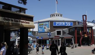 People visit Pier 39, where some stores, restaurants and attractions have reopened, during the coronavirus outbreak in San Francisco, Thursday, June 18, 2020. (AP Photo/Jeff Chiu)