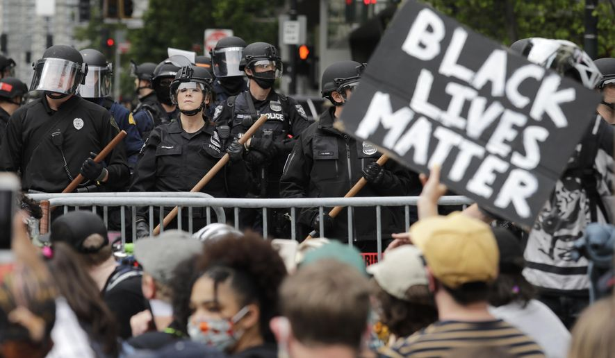 In this June 3, 2020, file photo, police officers behind a barricade look on as protesters fill the street in front of Seattle City Hall, in Seattle, following protests over the death of George Floyd, a black man who was in police custody in Minneapolis. The King County Labor Council, the largest labor group in the Seattle area, vote Wednesday night June 17 to expell the city's police union, saying the guild representing officers failed to address racism within its ranks. (AP Photo/Elaine Thompson, File)