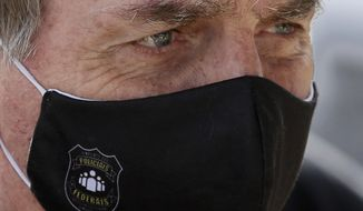 FILE - In this May 26, 2020 file photo, Brazil's President Jair Bolsonaro, wearing a face mask with a logo of the Federal Police, leaves his official residence of Alvorada Palace in Brasilia, Brazil. Bolsonaro won the presidency in 2018 with a campaign that emphasized law and order, and said police should be able to kill criminals with almost no legal constraints in order to curb homicides. (AP Photo/Eraldo Peres, FIle)