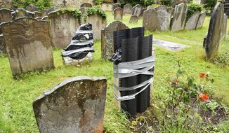"""The damaged headstone and footstone on the grave of an enslaved African man, in St Mary's churchyard, in Bristol, England, Thursday June 18, 2020, which have been vandalised in an apparent """"retaliation attack"""" following the toppling of a statue of slave trader Edward Colston during anti-racist protests held in the wake of the killing of George Floyd in the US. The Grade II-listed, brightly painted memorial to Scipio Africanus have been smashed and a message was scrawled in chalk on flagstones nearby. (Ben Birchall/PA via AP)"""