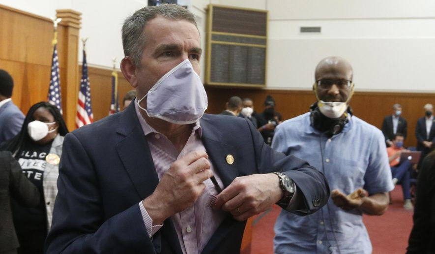 Virginia Gov. Ralph Northam, left, dons a mask as he leaves a news conference after announcing his plans to remove the statue of Confederate General Robert E. Lee on Monument Avenue Thursday, June 4, 2020, in Richmond, Va. (AP Photo/Steve Helber) ** FILE **