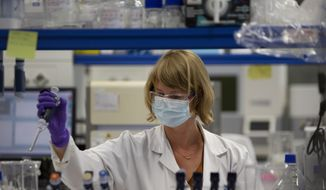 A lab technician works during research on coronavirus, COVID-19, at Johnson & Johnson subsidiary Janssen Pharmaceutical in Beerse, Belgium, Wednesday, June 17, 2020. Janssen Pharmaceutical hopes to begin clinical trials on a potential vaccine for COVID-19 in the middle of the summer. (AP Photo/Virginia Mayo) **FILE**