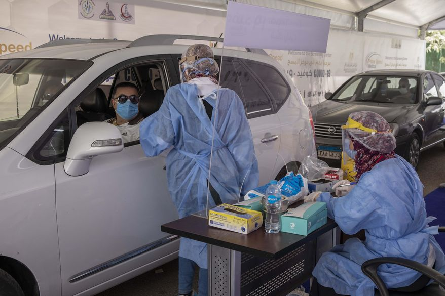 A health worker wearing protective gear prepares to take swab samples from people queuing in their cars to test for the coronavirus at a drive-through COVID-19 screening center at Ain Shams University in Cairo, Egypt, Wednesday, June 17, 2020. (AP Photo/Nariman El-Mofty)